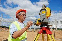 Surveyor works with theodolite. One surveyor worker working with theodolite transit equipment at road construction site outdoors Royalty Free Stock Photos