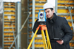 Surveyor works with theodolite. One surveyor worker working with theodolite transit equipment at road construction site outdoors Stock Photos