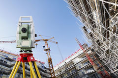 Surveyors measuring instrument and construction. Close-ups of surveyors measuring instrument, standing on tripod inside super-wide view of construction site Stock Photo