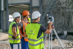 Surveyors work with a total station stock image
