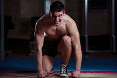 Survival Of The Fittest. Strong Muscular Men Without The Shirt Kneeling On The Floor - Almost Like Sprinter Starting Position Royalty Free Stock Photography