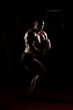 Survival Of The Fittest. Serious Bodybuilder Standing In The Gym And Flexing Muscles Royalty Free Stock Photos