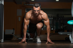 Survival Of The Fittest. Strong Muscular Men Kneeling On The Floor - Almost Like Sprinter Starting Position Royalty Free Stock Images