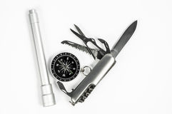 Survival kit. Compass, utility knife, flash light as survival kit on white background without the container stock photography