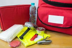 Survival kit. Emergency kit for survival in case of disaster including water, first aid kit, lighter, bags, utility knife and others Stock Image