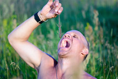 Survival in the wild. Hungry man wants to eat a lizard. Royalty Free Stock Photography
