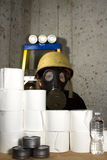 Survivalist. Woman dressed in gas mask and hard hat hiding in the basement with stockpiled goods Royalty Free Stock Photo