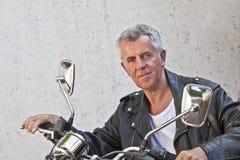 Survivez au cavalier battu de visage reposé sur une moto Photographie stock libre de droits