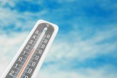 Survivez au thermomètre et au ciel nuageux bleu sur le fond image libre de droits