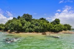 Survivor. An island with beautiful green waters and a clear blue sky Royalty Free Stock Images