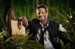 Survivor businessman leaning to a sign in the jungle Stock Photos