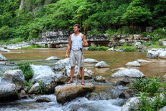 Survivor man in jungle river. Muscular adventurous Caucasian man in tank top and shorts holding spear while standing triumphantly on boulder in middle of river Stock Photos