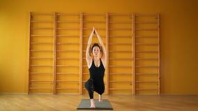 Surya namaskar Женщина в черном bodysuit делая практику йоги в желтой студии на предпосылке лестниц Здоровье, образ жизни видеоматериал