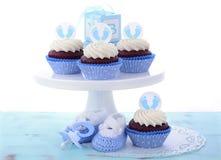 Sus magdalenas azules de una fiesta de bienvenida al bebé del muchacho Foto de archivo