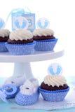 Sus magdalenas azules de una fiesta de bienvenida al bebé del muchacho Foto de archivo libre de regalías