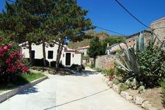 Susak village near Mali Losinj in Croatia. Street and homes wit gardens,oleanders and agavas in Susak Stock Images