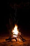Susciter le feu de camp pendant la nuit Photographie stock libre de droits
