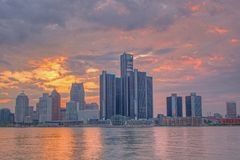 Suset Behind Detroit, Michigan Skyline From Windsor, Ontario. The setting sun lights up the clouds behind the skyline of downtown Detroit, Michigan. The stock photo