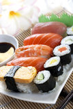 Sushi. Plate of sushi, with soy sauce and chopsticks, over bamboo background Royalty Free Stock Image