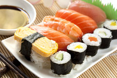 Sushi. Plate of sushi, with soy sauce and chopsticks, over bamboo background Royalty Free Stock Photo