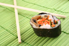Sushi. Single piece of sushi with chopsticks on green mat, narrow focus Royalty Free Stock Image