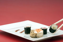 Sushi. A selection of Sushi on a white rectangular plate with a red background Stock Image