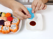 Sushi. Closeup image of hand prepare japanese food sushi and sauce on white table Stock Image