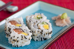 Sushi. Four roll of sushi, wasabi and ginger on a blue plate and red background Stock Image