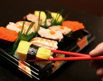 Sushi. Delicious sushi man hand holding chopsticks Royalty Free Stock Photography