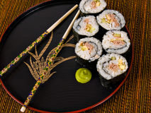 Sushi. On a Japanese plate with chopsticks royalty free stock photo