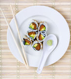 Sushi. Raw fish and avocado sushi on a white plate with chopsticks and wasabi stock image
