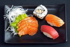 Sushi. And sashimi served on black plate Stock Images