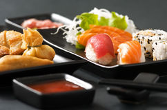 Sushi. And sashimi served on black plate Royalty Free Stock Photography