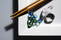 Sushi?. China sticks to the white, square plate with glass balls stock photography
