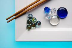 Sushi?. China sticks to the white, square plate with glass balls Royalty Free Stock Photo