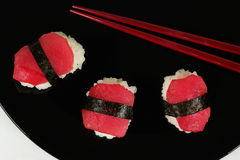 Sushi. Three pieces of sushi on black plate with chopsticks Royalty Free Stock Photos