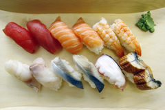 Sushi. Japanese Food - a variety of traditional raw sushi and wasabi served on a wooden tray Royalty Free Stock Images