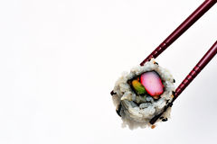 Sushi. California sushi roll being held with a chopstick Royalty Free Stock Photography