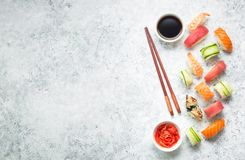 Sushi assorted set. Assorted sushi set on white concrete background. Space for text. Japanese sushi, rolls, soy sauce, ginger, chopsticks. Top view. Sushi nigiri stock photo