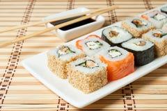 Sushi Assortment On White Dish over bamboo background. Stock Photos