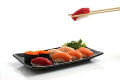 Sushi auf dem schwarzen Teller getrennt im weißen Hintergrund Stockbild