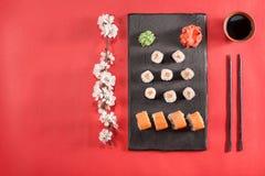Sushi auf Platte mit Essstäbchen, Ingwer, Sojabohnenöl, Wasabi und Kirschblüte Lizenzfreie Stockfotografie