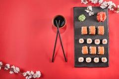 Sushi auf Platte mit Essstäbchen, Ingwer, Sojabohnenöl, Wasabi und Kirschblüte Lizenzfreies Stockfoto
