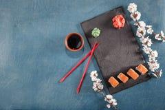 Sushi auf Platte mit Essstäbchen, Ingwer, Sojabohnenöl, Wasabi und Kirschblüte Stockfoto