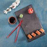 Sushi auf Platte mit Essstäbchen, Ingwer, Sojabohnenöl, Wasabi und Kirschblüte Stockbild