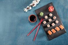 Sushi auf Platte mit Essstäbchen, Ingwer, Sojabohnenöl, Wasabi und Kirschblüte Lizenzfreie Stockbilder