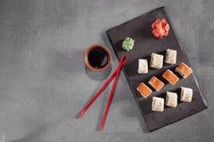 Sushi auf Platte mit Essstäbchen, Ingwer, Sojabohnenöl, Wasabi und Kirschblüte Stockbilder