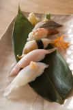 Sushi on a Banana Leaf. Photographs of sushi on a banana leaf on a square plate on a wood table stock photos