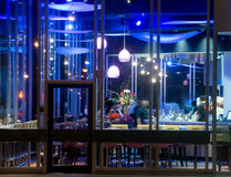 Sushi Bar at Night. Modern urban sushi bar at night.  Large window space provide view into restaurant where a chef works and diners enjoy a meal Stock Photos