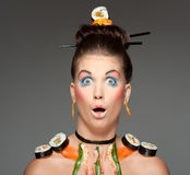 Sushi beauty. A creative and colorful image of a fashion model wearing asian themed makeup and raw sushi stock image